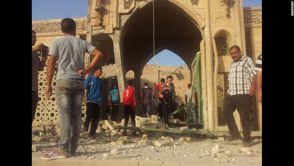 People inspect the destroyed mosque in Mosul. Militants overran Iraq's second-largest city in June and imposed their harsh interpretation of Islamic law.