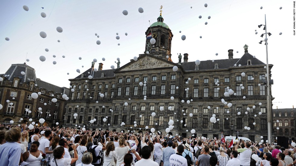 """JULY 25 - AMSTERDAM: People release white balloons into the air during a silent march in memory of the victims of the <a href=""""http://edition.cnn.com/SPECIALS/world/mh17-specials-page/index.html?hpt=hp_inthenews"""">downed Malaysia Airlines flight MH17</a>."""