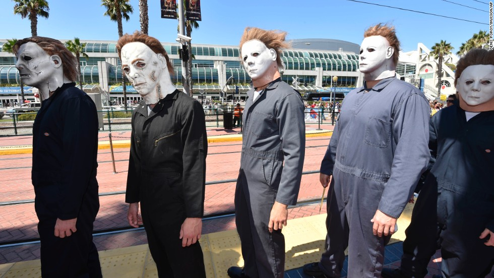 "People dressed as Michael Myers from the ""Halloween"" films wait at a trolley stop outside of the San Diego Convention Center on July 24."