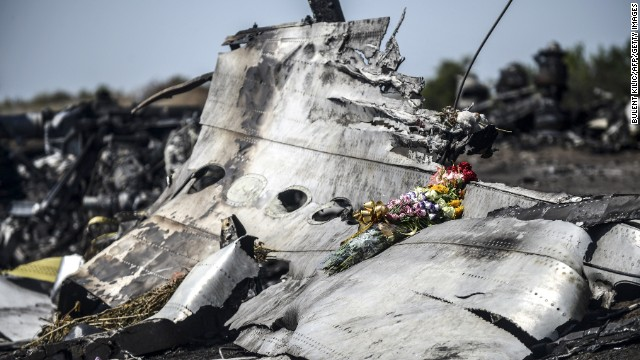 caption:This photo taken on July 26, 2014 shows flowers, left by parents of an Australian victim of the crash, laid on a piece of the Malaysia Airlines plane MH17, near the village of Hrabove (Grabove), in the Donetsk region. Ukraine sought on July 25 to avoid a political crisis after the shock resignation of its prime minister, as fighting between the army and rebels close to the Malaysian airliner crash site claimed over a dozen more lives. Dutch and Australian forces were being readied on July 26 for possible deployment to secure the rebel-held crash site of the Malaysia Airlines flight MH17 in east Ukraine where many victims' remains still lie nine days after the disaster claimed 298 lives. AFP PHOTO/ BULENT KILIC (Photo credit should read BULENT KILIC/AFP/Getty Images)
