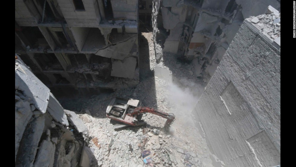 A man clears debris at the site of an alleged barrel-bomb attack in Aleppo on Tuesday, July 15.