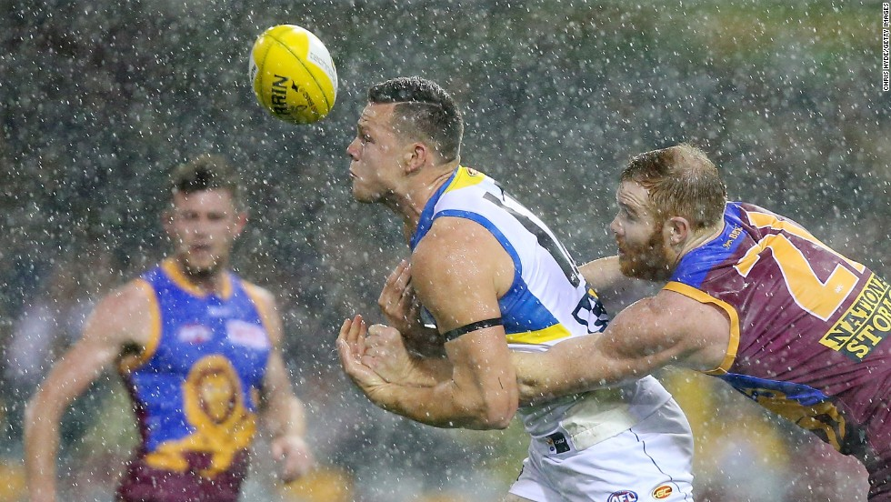 Steven May of the Gold Coast Suns is tackled by Daniel Merrett of the Brisbane Lions during an Australian Football League match played Saturday, July 26, in Brisbane, Australia.