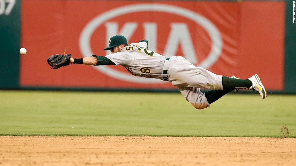 Oakland Athletics second baseman Eric Sogard stretches out as he tries to grab a ball hit by Texas' Alex Rios in the fifth inning of a Major League Baseball game Sunday, July 27, in Arlington, Texas.