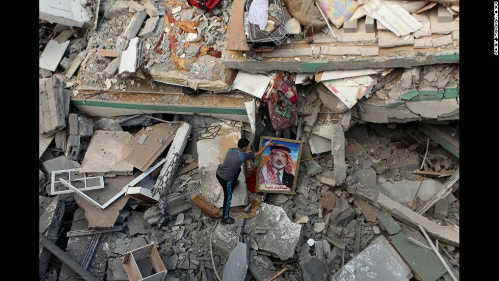 A Palestinian man places a portrait of Hamas leader Ismail Haniya on the rubble of Haniya's Gaza City home July 29 after it was hit by an overnight airstrike.