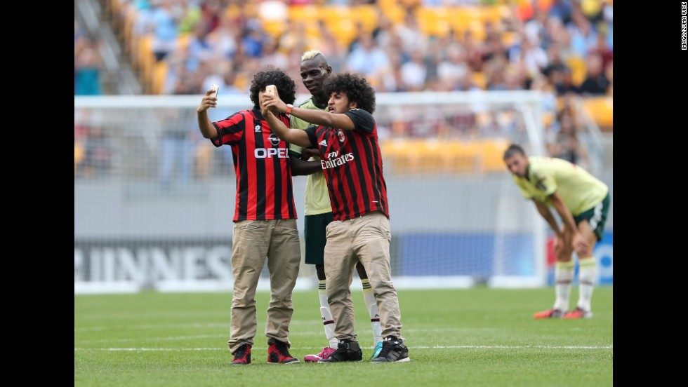 Two AC Milan fans invade the field at Pittsburgh's Heinz Field to get a selfie with Milan forward Mario Balotelli on Sunday, July 27. The Italian soccer team was playing the last few minutes of a preseason match against English club Manchester City.