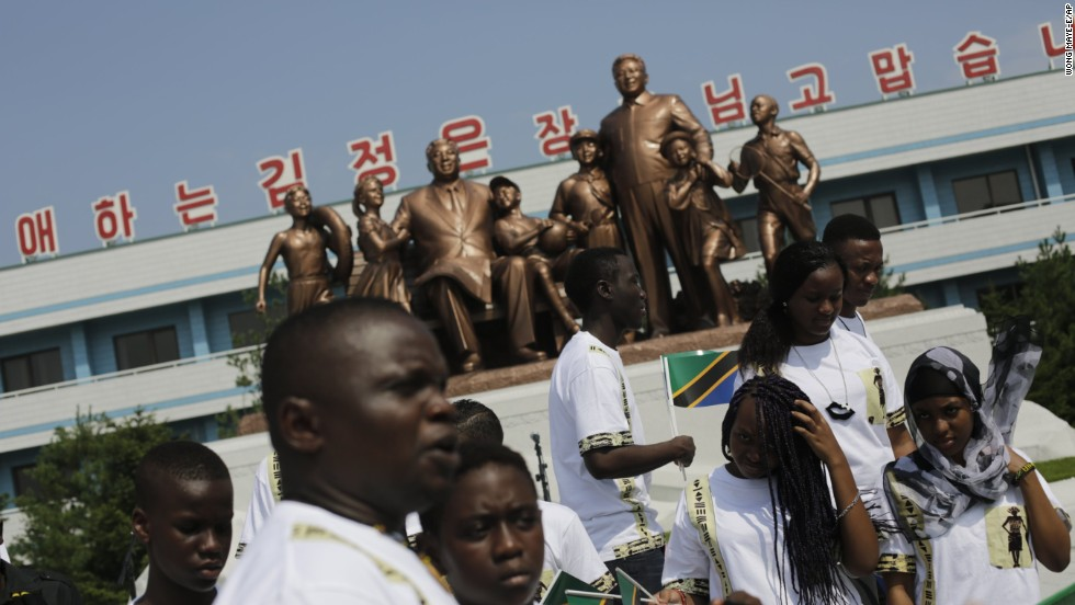 Students from the Laureat International School in Tanzania walk past a statue of the late North Korean leaders Kim Il Sung and Kim Jong Il.