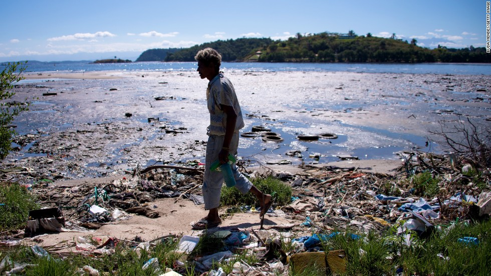 JULY 31 - NITEROI, BRAZIL - JULY 30: A man walks along the polluted waters of Guanabara Bay, the future site of sailing events during the Rio 2016 Olympic Games. Rio's Olympic bid included the promise to clean up the bay. But officials say only a third of Rio's sewage is currently treated, while the remainder flows untreated into the waters.