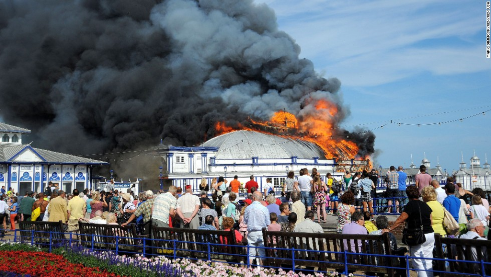 Onlookers watch a fire at the Eastbourne Pier in Eastbourne, England, on Wednesday, July 30.