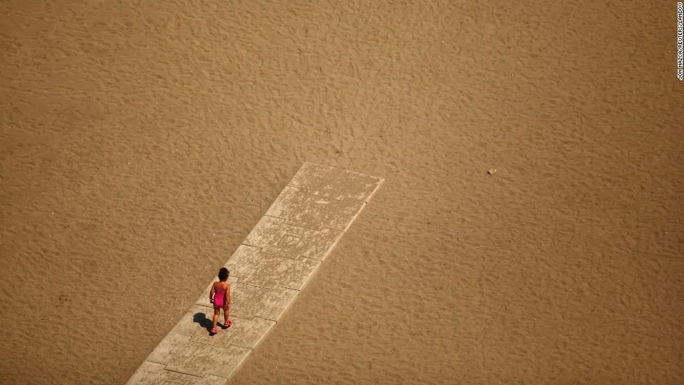 A child walks toward the shore of the Mediterranean Sea at Malagueta Beach in Malaga, Spain, on Sunday, July 27.