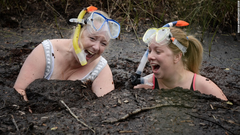 "Two women take a dip in the ""Bog Jacuzzi"" after taking part in the Irish Bog Snorkeling championship on Sunday, July 27, in Dungannon, Northern Ireland."