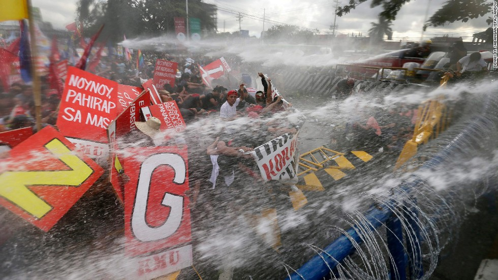 Anti-riot police officers use water cannons to disperse protesters attempting to reach the Philippine Congress in Quezon City, Philippines, on Monday, July 28, during the state of the nation address by President Benigno Aquino.