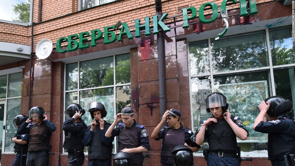 Sberbank is Russia's biggest lender and the 186th largest company globally. It reported $54.8 billion in revenues last year and $11 billion in net profit, according to its Fortune Global 500 ranking. Pictured here are policemen guarding a branch of Sberbank in Kiev.