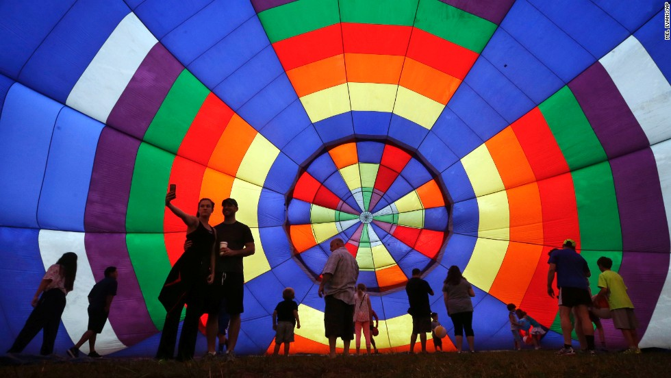 People walk around inside a partially inflated hot air balloon at the 32nd annual QuickChek New Jersey Festival of Ballooning, on Sunday, July 27, in Readington, New Jersey.
