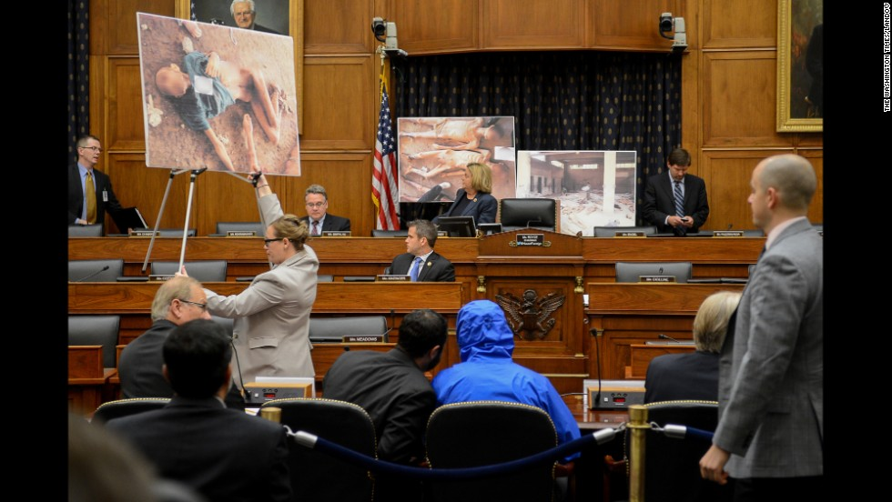 "Photographs of victims of the Bashar al-Assad regime are displayed as a Syrian Army defector known as ""Caesar,"" center, appears in disguise to speak before the House Foreign Affairs Committee. The briefing is called ""Assad's Killing Machine Exposed: Implications for U.S. Policy"" in Washington on Thursday, July 31. ""Caesar"" was apparently a witness to al-Assad's brutality and has smuggled more than 50,000 photographs depicting the torture and execution of more than 10,000 dissidents."