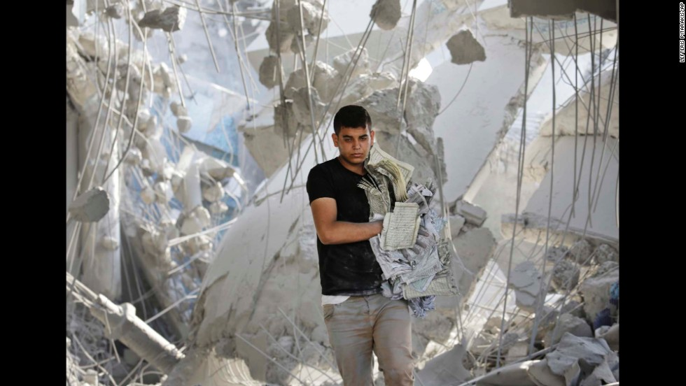 A young Palestinian carries damaged copies of the Quran from the rubble of the Imam Al Shafaey mosque in Gaza City on August 2.