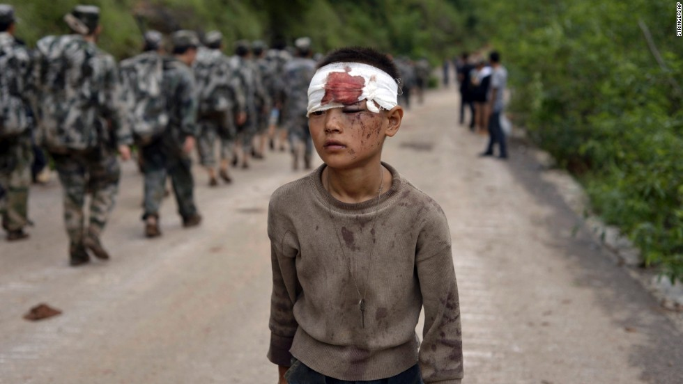 An injured child walks past rescuers heading toward the earthquake's epicenter on August 4.