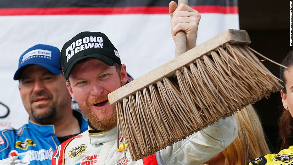 """NASCAR driver Dale Earnhardt Jr. holds up a broom Sunday, August 3, after winning the Sprint Cup race at Pocono Raceway in Long Pond, Pennsylvania. Earnhardt also won the June race at Pocono, completing the season """"sweep"""" at the track."""