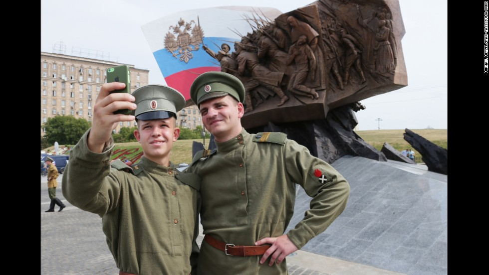 Two Russian soldiers pose in front of a new World War I memorial in Moscow on Saturday, August 2.