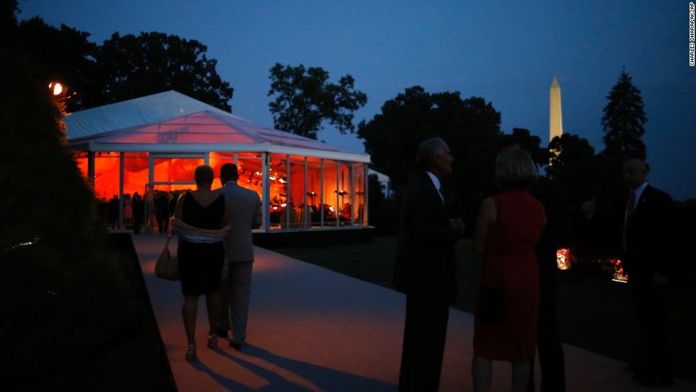 Guests gather outside a tent before dinner.
