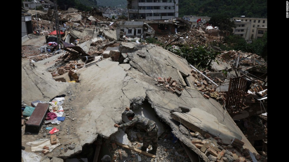 A military rescue worker searches for missing people in the rubble of destroyed houses in Longtoushan, a township in southwest China's Yunnan province, on Wednesday, August 6. The epicenter of a 6.1-magnitude earthquake was recorded in Longtoushan on Sunday, August 3. Hundreds of people have died since, state-run media reported.