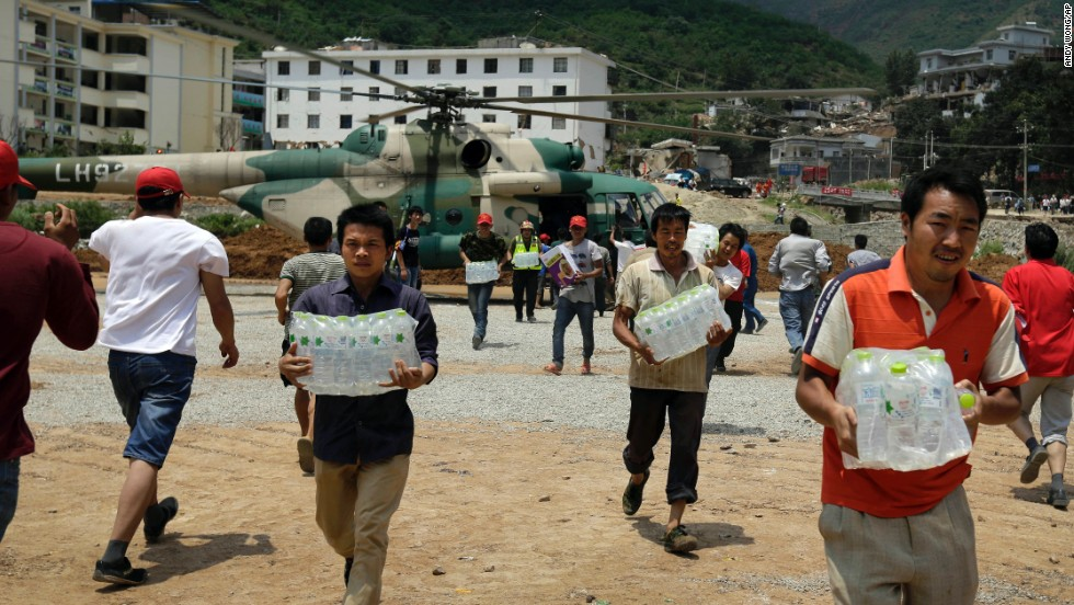 Volunteers deliver bottles of water brought by a helicopter to Longtoushan on August 6.