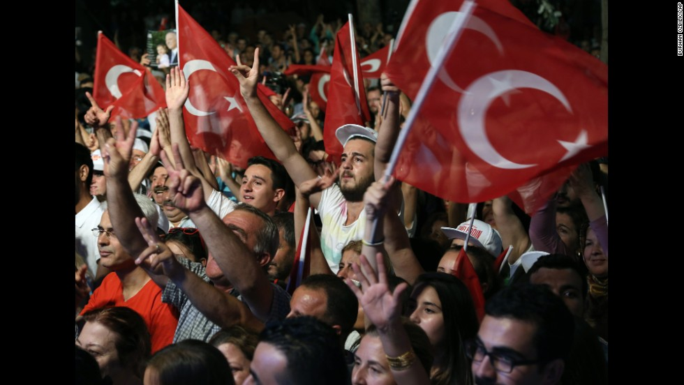 Supporters of Ekmeleddin Ihsanoglu, one of the leading opposition candidates for the presidential election, wave Turkish flags as they listen to him speak during a rally in Ankara on Monday, August 4.