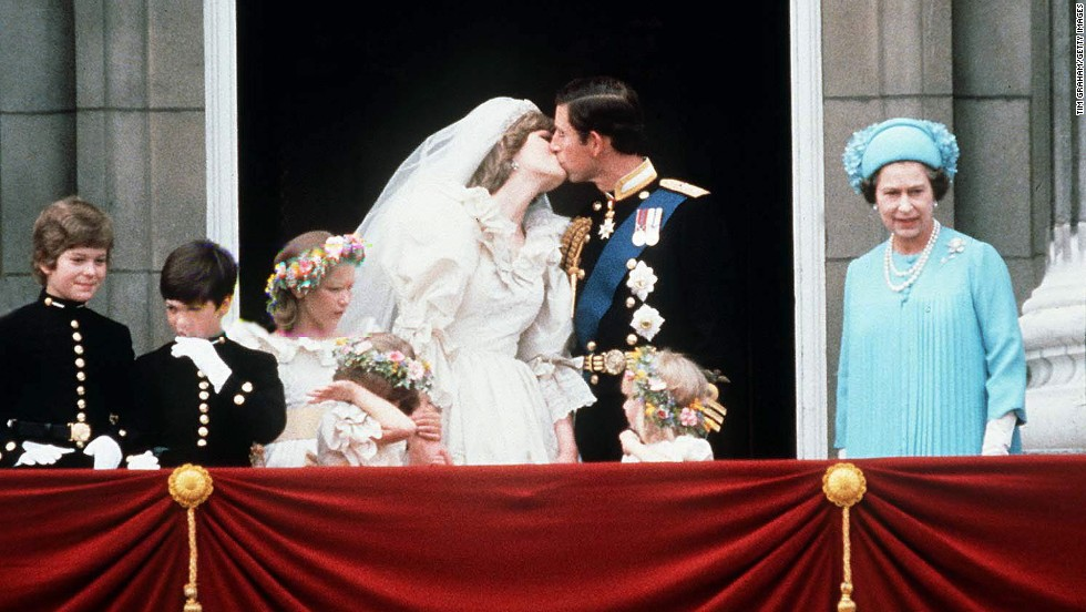The Queen stands next to Prince Charles as he kisses his new bride, Princess Diana, on their wedding day July 29, 1981.