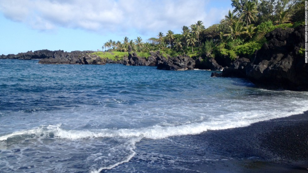Low volcanic cliffs surround a small black sand beach at Waianapanapa State Park, off the famous Hana Highway in Maui.