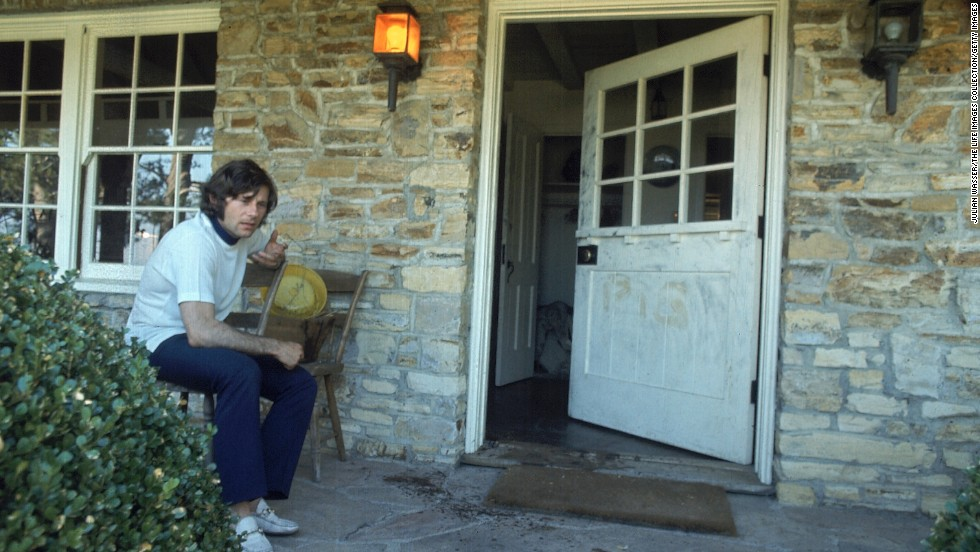 "Polanski, who was out of town at the time of the murders, is seen on the porch outside his home, the remnants of the word ""pig"" can be seen where it was scrawled on the door."