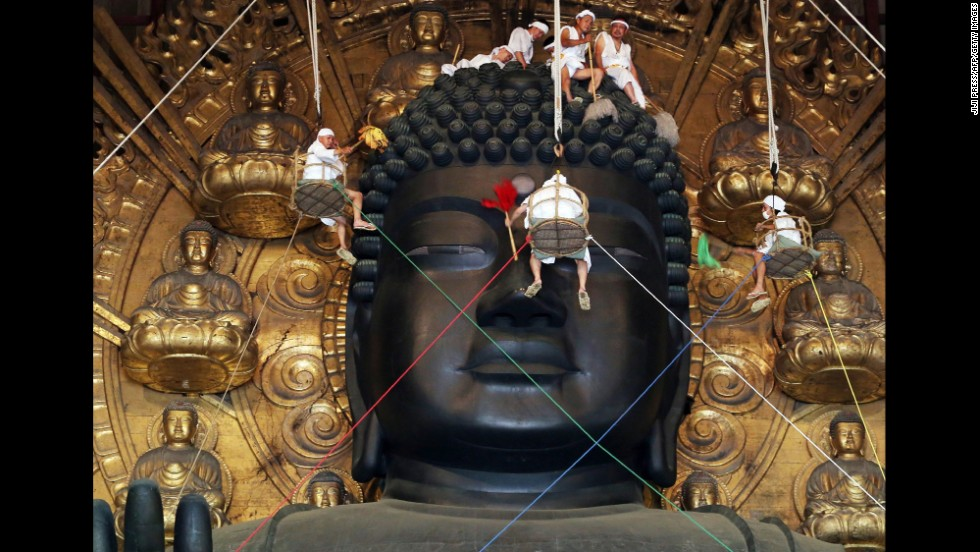 Buddhist monks and volunteers clean a Buddha statue that's nearly 50 feet tall Thursday, August 7, at Todaiji Temple in Nara, Japan.