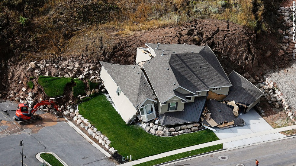 A home is destroyed Tuesday, August 5, following a landslide in a hillside community of North Salt Lake, Utah. At least a dozen other homes have been evacuated.