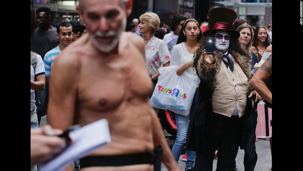 An entertainer dressed as the comic book character Penguin takes a photo of George Davis, who walked through New York's Times Square in the nude after giving a speech Wednesday, August 6. Davis, a candidate for the San Francisco Board of Supervisors, was speaking out against a public nudity ban in San Francisco that was introduced by his opponent, Scott Wiener.