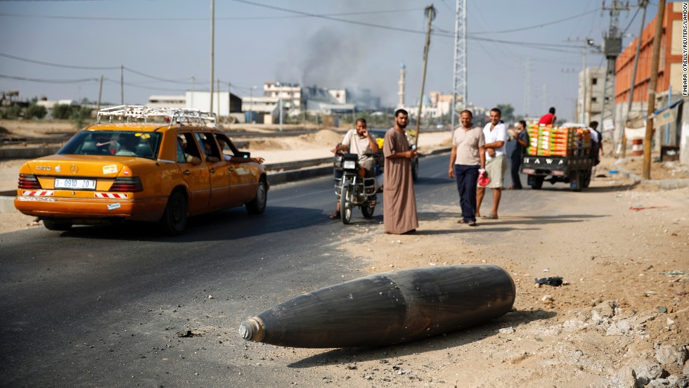 Palestinians look at an unexploded Israeli shell that landed on the main road outside the Gaza town of Deir al-Balah on Friday, August 1.