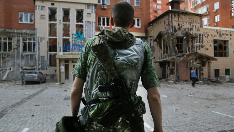A pro-Russian rebel inspects damage after shelling in Donetsk on Thursday, August 7.