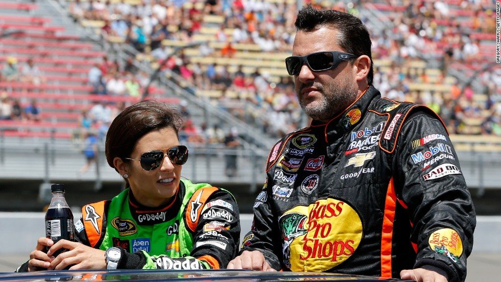 Stewart and Danica Patrick ride down pit road before a race in Brooklyn, Michigan, in June 2014.