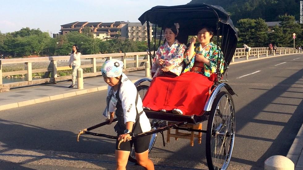 Kimono-clad Japanese tourists take a rickshaw ride over Arashiyama's Togetsukyo Bridge (Moon Crossing Bridge).