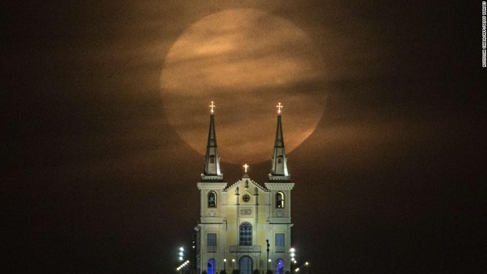 The moon descends behind the Nossa Senhora da Penha Church in Rio de Janeiro.