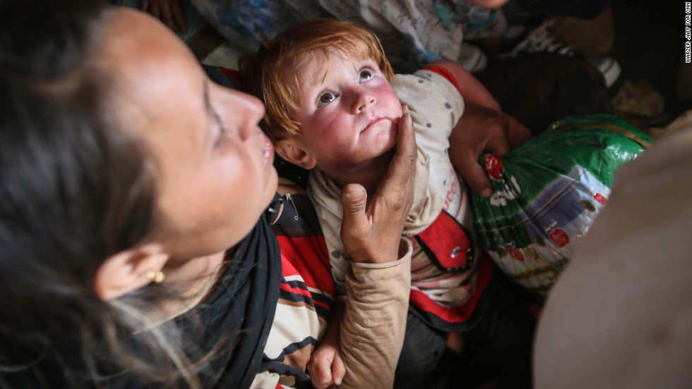 A toddler named Helen sits in her mother's lap after being rescued.