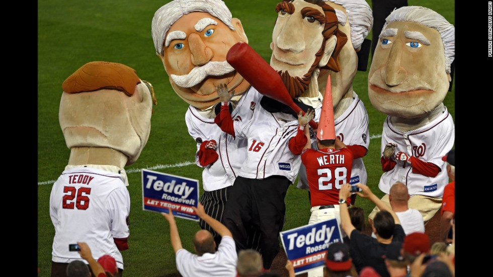 """A staff member of the Washington Nationals, dressed as the <a href=""""http://www.washingtonpost.com/blogs/dc-sports-bog/wp/2014/08/06/the-jayson-werth-garden-gnome-market-is-red-hot/"""" target=""""_blank"""">gnome giveaway</a> of Nationals outfielder Jayson Werth, hits Abraham Lincoln during the fourth-inning Presidents Race on Tuesday, August 5. The Presidents Race is a staple of every Nationals baseball game."""