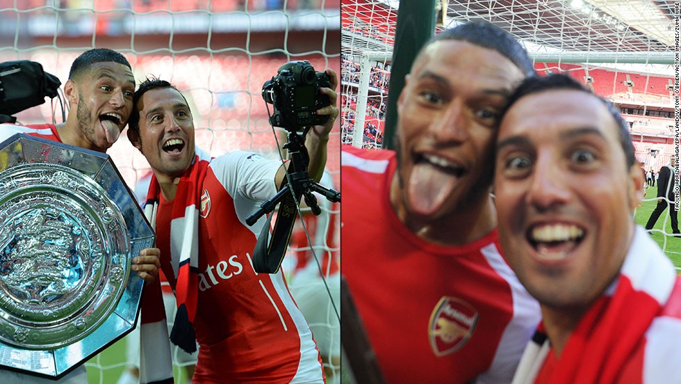 Soccer players Alex Oxlade-Chamberlain, left, and Santi Cazorla celebrate after Arsenal defeated Manchester City to win the FA Community Shield match Sunday, August 10, in London. The annual match pits the winners of the English Premier League against the winners of the FA Cup, England's oldest cup tournament.
