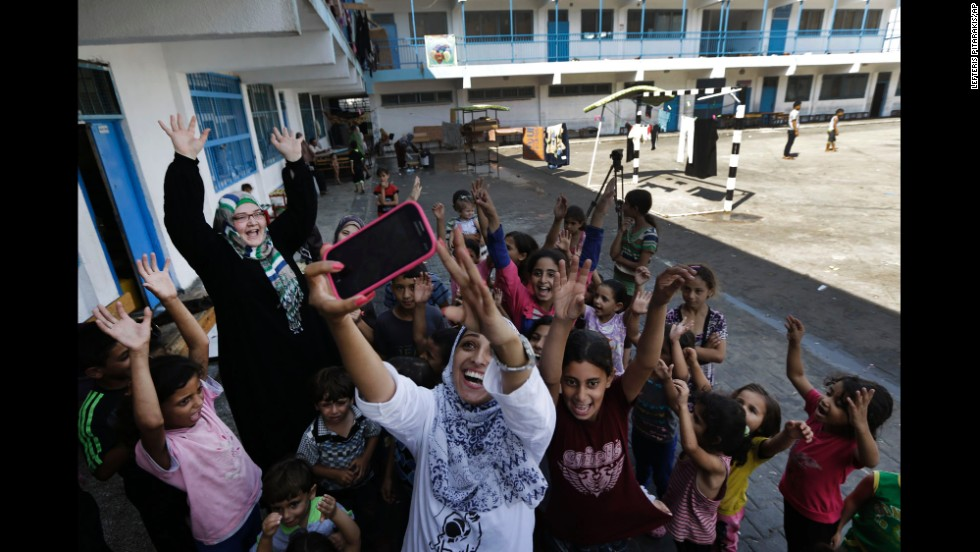 Nisreen Shawa uses her phone to take a photo with displaced Palestinian children at a United Nations school in Gaza City, Gaza, on Thursday, August 7.