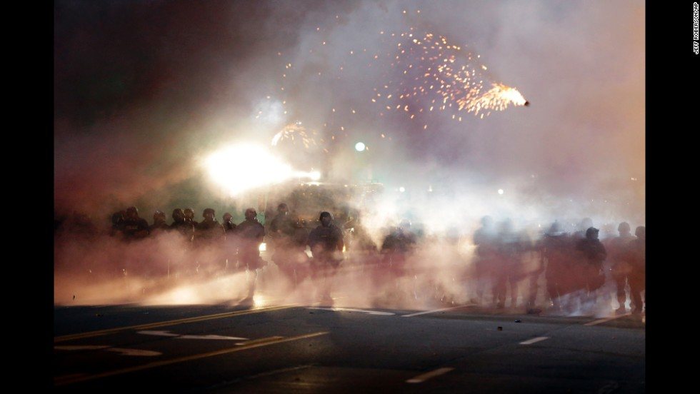 Police stand in clouds of smoke as they clash with protesters on August 13, 2014.