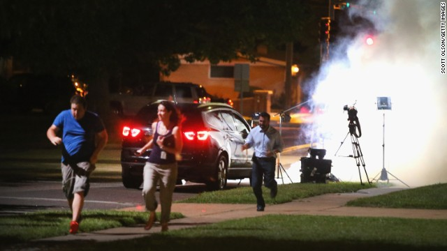 An Al-Jazeera television crew runs for cover as police fire tear gas at their position in Ferguson, Missouri, on August 13.