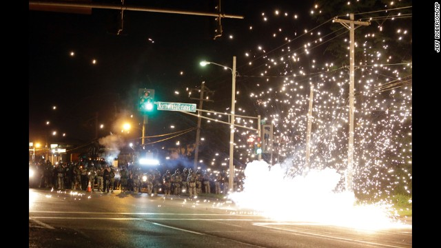 A device deployed by police goes off in the street as police and protesters clash Wednesday.