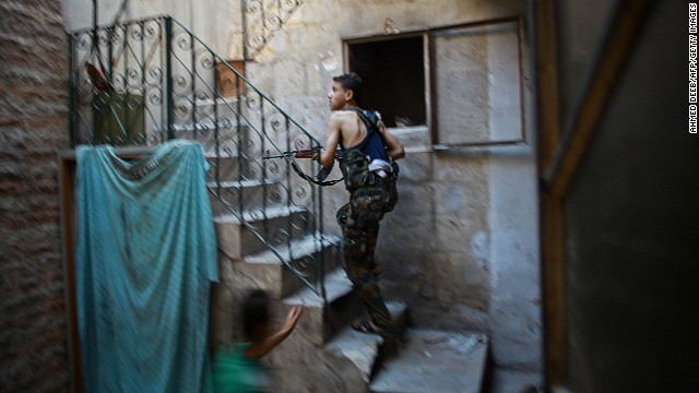A fighter from the Islamic Front takes position in a building during clashes with Syrian regime forces Aleppo on July 21.