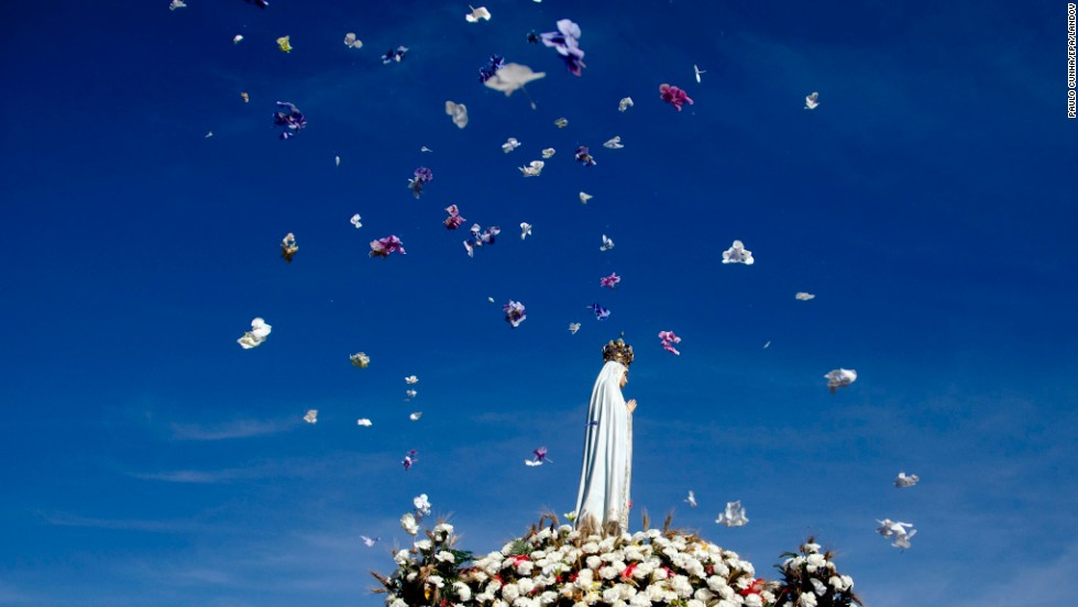 "Flowers are thrown in the air Wednesday, August 13, as the Our Lady of Fatima statue is carried during a pilgrimage to Fatima Sanctuary in Fatima, Portugal. It is one of the world's most important Catholic shrines dedicated to the Virgin Mary, according to <a href=""http://www.portugal.com/fatima/"" target=""_blank"">Portugal.com.</a>"