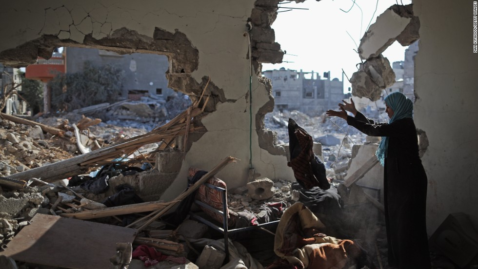 Islam El Masri begins to sort through the rubble of her destroyed home in Beit Hanoun, Gaza, on Thursday, August 14.
