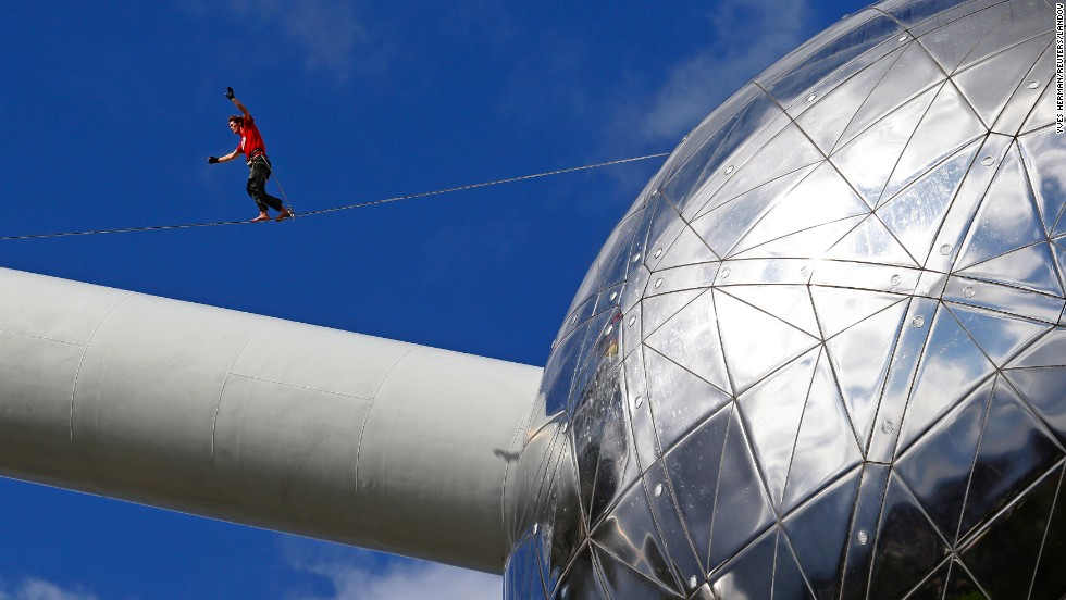 "A tightrope walker performs between two spheres of the <a href=""http://atomium.be"" target=""_blank"">Atomium monument</a> in Brussels, Belgium, on Monday, August 11. The 335-foot-tall structure is shaped like a unit cell of an iron crystal that has been magnified about 165 billion times."