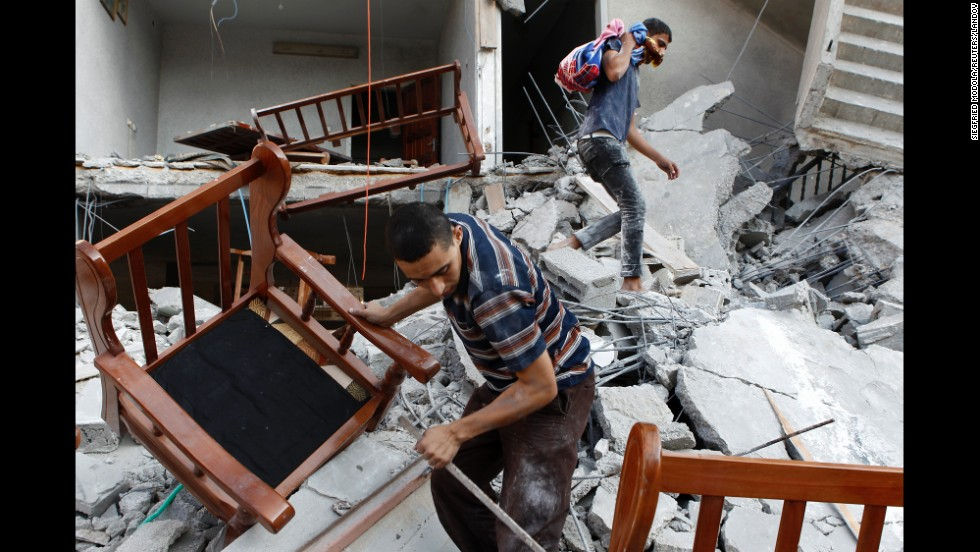 Men salvage belongings from the ruins of a Gaza City home that residents say was hit by an Israeli airstrike on Saturday, August 9.