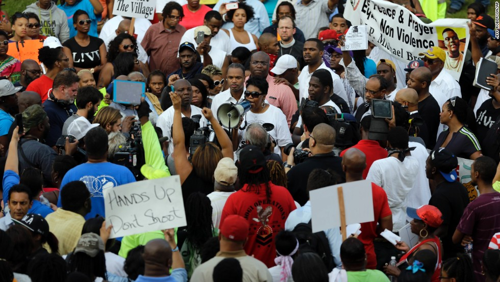 The Rev. Traci Blackmon uses a megaphone to talk to a large group of demonstrators on August 14, 2014.